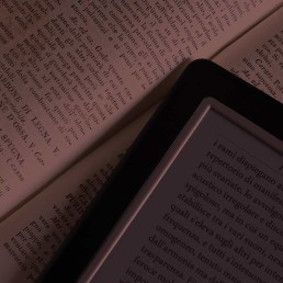 A page of a book (possible a foreign language dictionary) with an e-reader device showing similar content on the screen