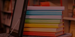 Some blank books with a tablet and stylus in front, books have no writing on the spine, they are colourful